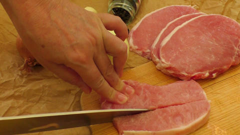 Slicing meat on a wooden cutting board Footage