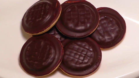 Cookies covered with chocolate, on a white plate Footage