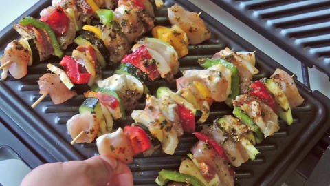 Shashlik skewered chicken meat with vegetables on electric grill Footage