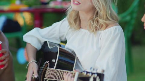 Close up of young woman playing at the guitar with his friends. Group of friends Live Action