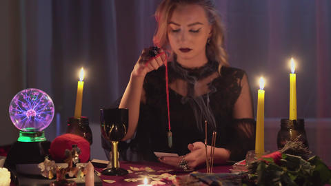 Female fortune teller holding a magic pendulum over a candle Live Action