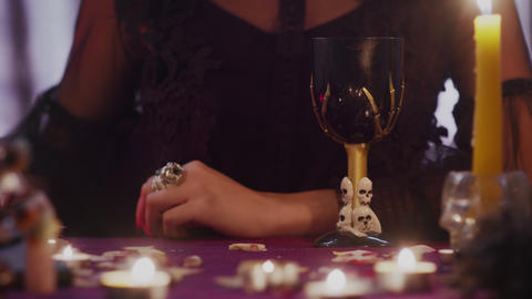Female fortune teller moving a magic taro card over a candle Live Action