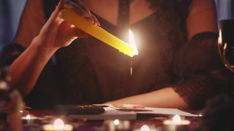 Witch fortune teller psychic moves candle near photo with lost person, and then Live Action