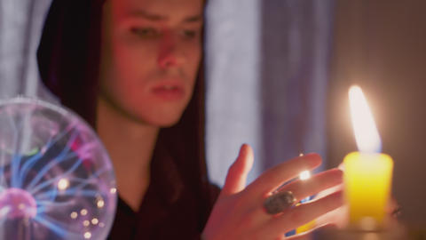 Side view of male fortune teller moving hands above the magic candle Live Action