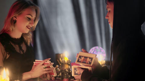 Witch and male wizard are dealing cards and reading future and fortune of Live Action