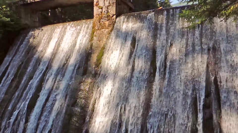 Concrete dam wall with falling waterfall stream in the forest Footage