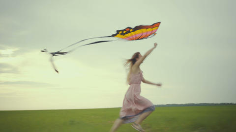 girl running around with a kite on the field. Freedom concept Live Action