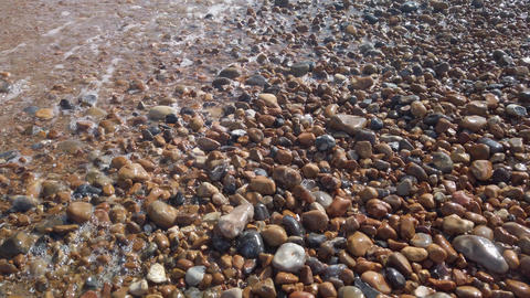 Real time of waves over pebbles on Brighton beach, England Live Action