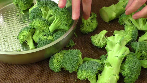 Female hands cutting broccoli in kitchen. Healthy food Live Action