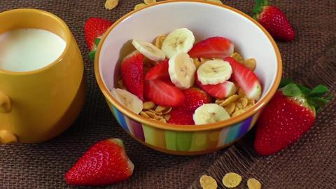 Healthy breakfast. Cornflakes, fresh strawberries, banana and milk Footage