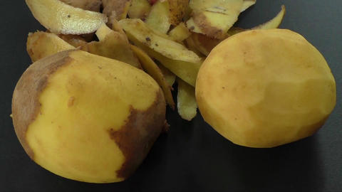 Peeled potatoes and potato peel on the black background Footage