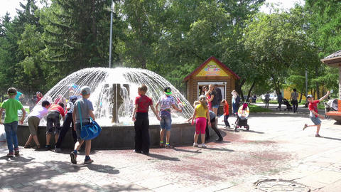 People resting hot summer day at water fountain in downtown Footage