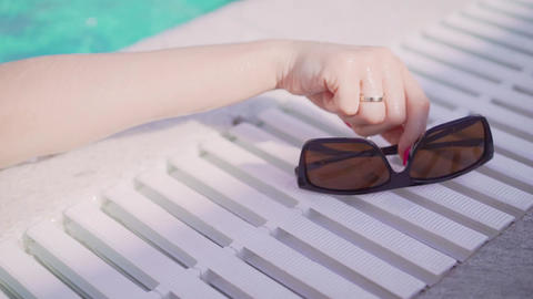 The girl takes sunglasses by the pool. Girl and sunglasses Live Action