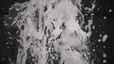 The water in the fountain splashes against a black background Live Action