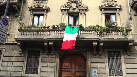 Europe, Italy , Milan - Flag of Italy hanging on the balcony during n-cov19 Coronavirus epidemic Live Action