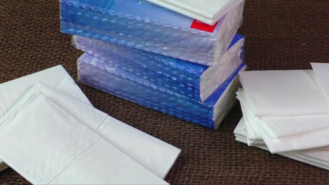 Pile of paper handkerchief pockets isolated on brown background Footage