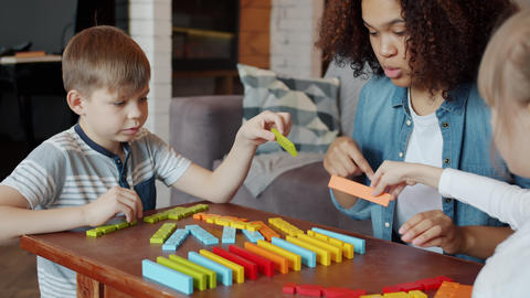 Caring babysitter Afro-American lady playing toys with smart obedient children Live Action