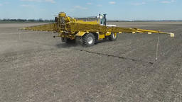 Aerial drone travelling up behind fertilizer as it travels across a field Live Action