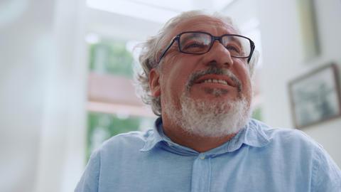 Emotional senior man smiling at home. Closeup mature man with positive emotion Live Action