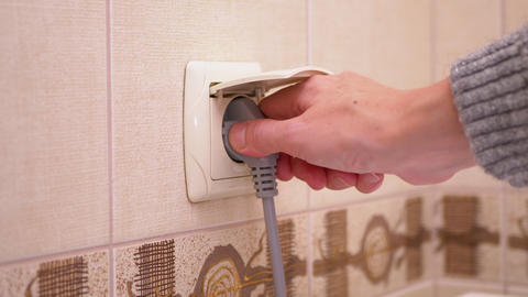 Side View of Female Hand Unplugging Electrical Outlet in Bathroom Live Action