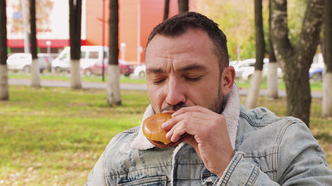 A man in a denim jacket is leisurely eating a burger in the park Live Action