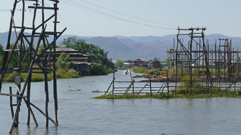 Long boats float between stilted houses on Inle Footage