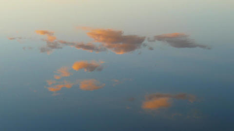 Reflection of sunset clouds in quiet water Footage
