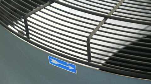 Industrial cooler propeller hidden under safety bar. Electric Industrial Fan Live Action