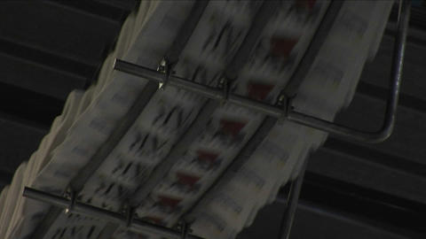 A fast zoom into newspapers moving along the top of an assembly line Footage