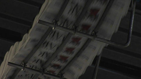 A fast zoom into newspapers moving along the top of an... Stock Video Footage
