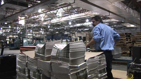 A worker stacks newspapers at a printing factory Stock Video Footage
