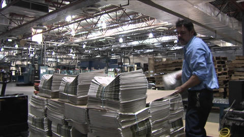 A worker stacks newspapers at a printing factory Footage