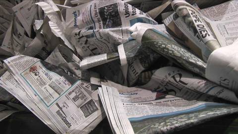 Pan across old crinkled newspapers sit in a recycling bin in a factory Footage