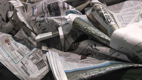Pan across old crinkled newspapers sit in a recycling bin... Stock Video Footage