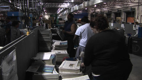 Workers in a newspaper factory sort and stack papers Footage