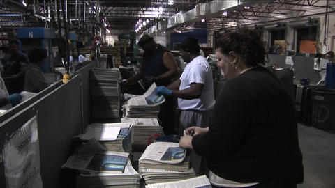 Workers in a newspaper factory sort and stack papers Stock Video Footage