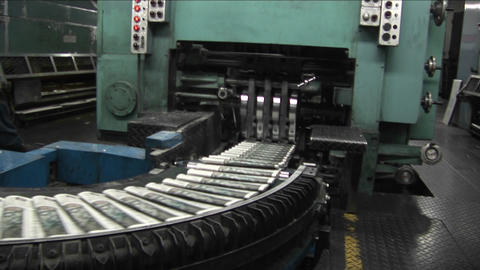 Newspapers move along an assembly line in a factory Footage