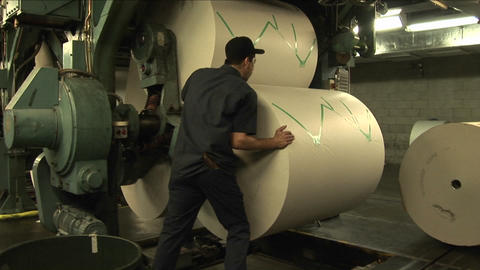 Workers load paper rollers in newspaper factory Footage