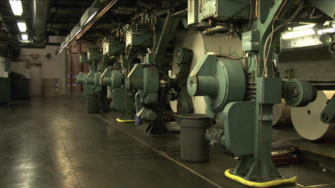 Workers watch paper rollers in newspaper factory Stock Video Footage