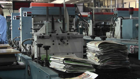 Workers man the printing presses in a newspaper factory Stock Video Footage