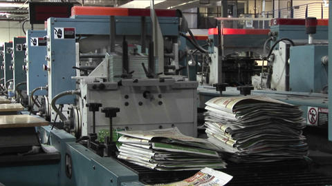 Workers man the printing presses in a newspaper factory Footage