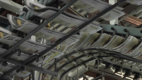 Newspapers flow along an assembly line in a newspaper factory Footage
