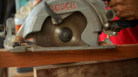 A circular saw cuts through wood at a workbench Stock Video Footage
