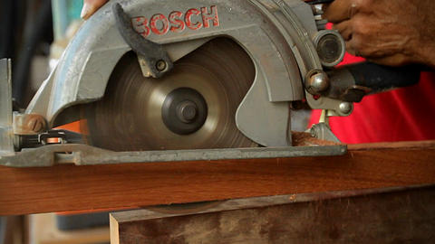 A circular saw cuts through wood at a workbench Footage