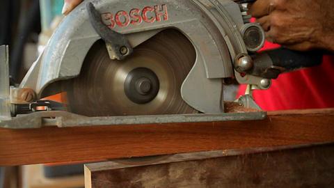 A circular saw cuts through wood at a workbench Footage