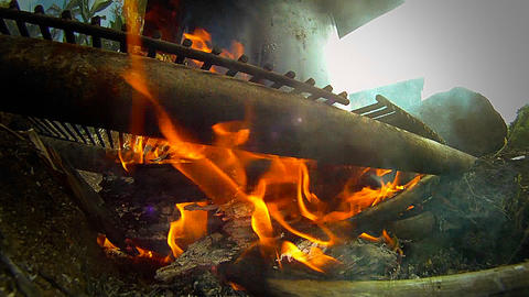 A fire burns under a kettle in a campground Stock Video Footage