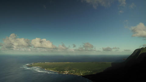Time lapse of clouds over a mountaintop and beach  Footage