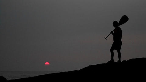 Native Hawaiian walks in silhouette holding a padd Stock Video Footage