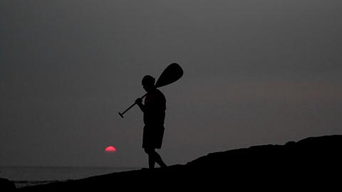 Native Hawaiian walks in silhouette holding a padd Footage
