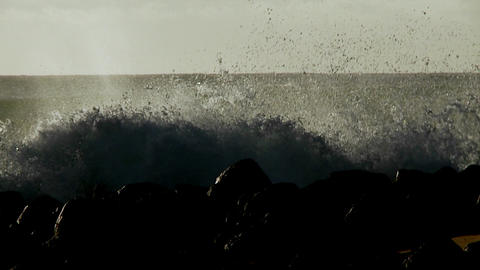 Large waves crest and break on a shoreline Footage